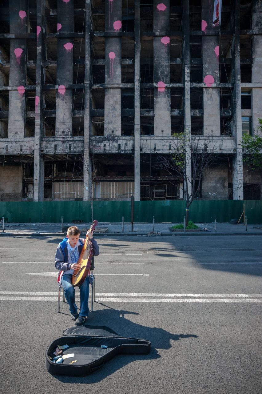 Ukraina, Kiev/Kyiv. Vid det stora Frihets-torget, Majdan, i centrala Kiev står det gamla fackföreningarnas hus – helt urblåst efter en brand i samband med det krigsliknande tillståndet på torget. Den unga mannen, i den broderade skjortan vyshyvanka, spelar på det traditionella stränginstrumentet bandura. Det är ett slags luta, som enligt traditionen spelas av de kringvandrande berättarna, trubadurerna, kobzar. Berättelserna handlar om allt från krig till kärlek, men har ofta en lyrisk ton. Foto: Johan Lindstén