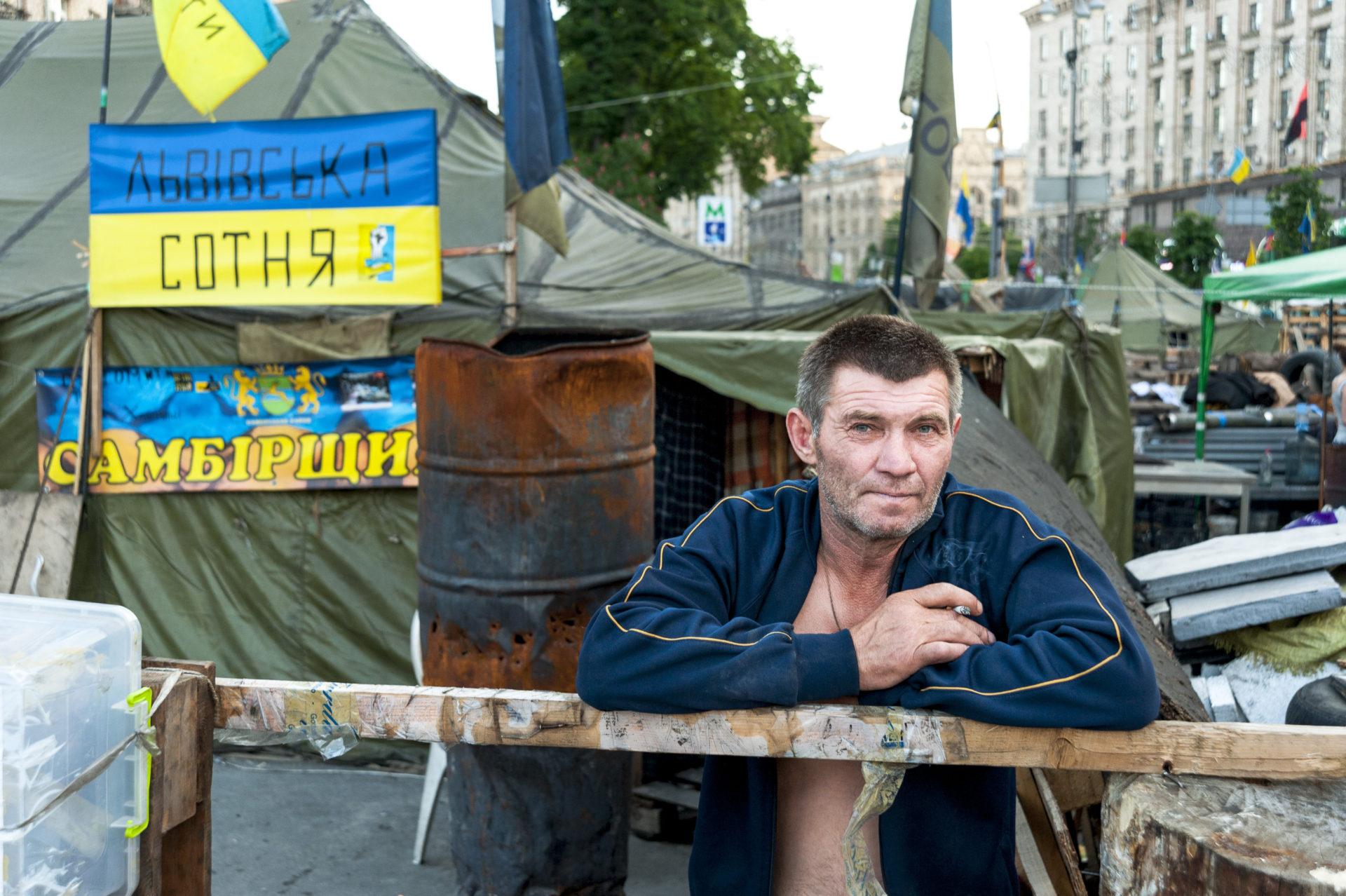 Ukraina, Kiev/Kyiv. Spåren av sammandrabbningarna på det stora, stolta torget Majdan i centrala Kiev var länge tydliga. I dag, 2017, är det mesta bortrensat. Bilden är från maj 2014, då barrikaderna ännu stod på plats innan folket på torget kunde avveckla sin bevakning efter presidentvalet och installationen av chokladmagnaten Petro Porotjenko. Mannen på bilden kallade sig Alexander, och hade kommit till huvudstaden och Maydan från staden Lviv, alldeles intill den polska gränsen. Han slogs mot polis och paramilitära trupper för att på så sätt avsätta den förra makten. Foto: Johan Lindstén