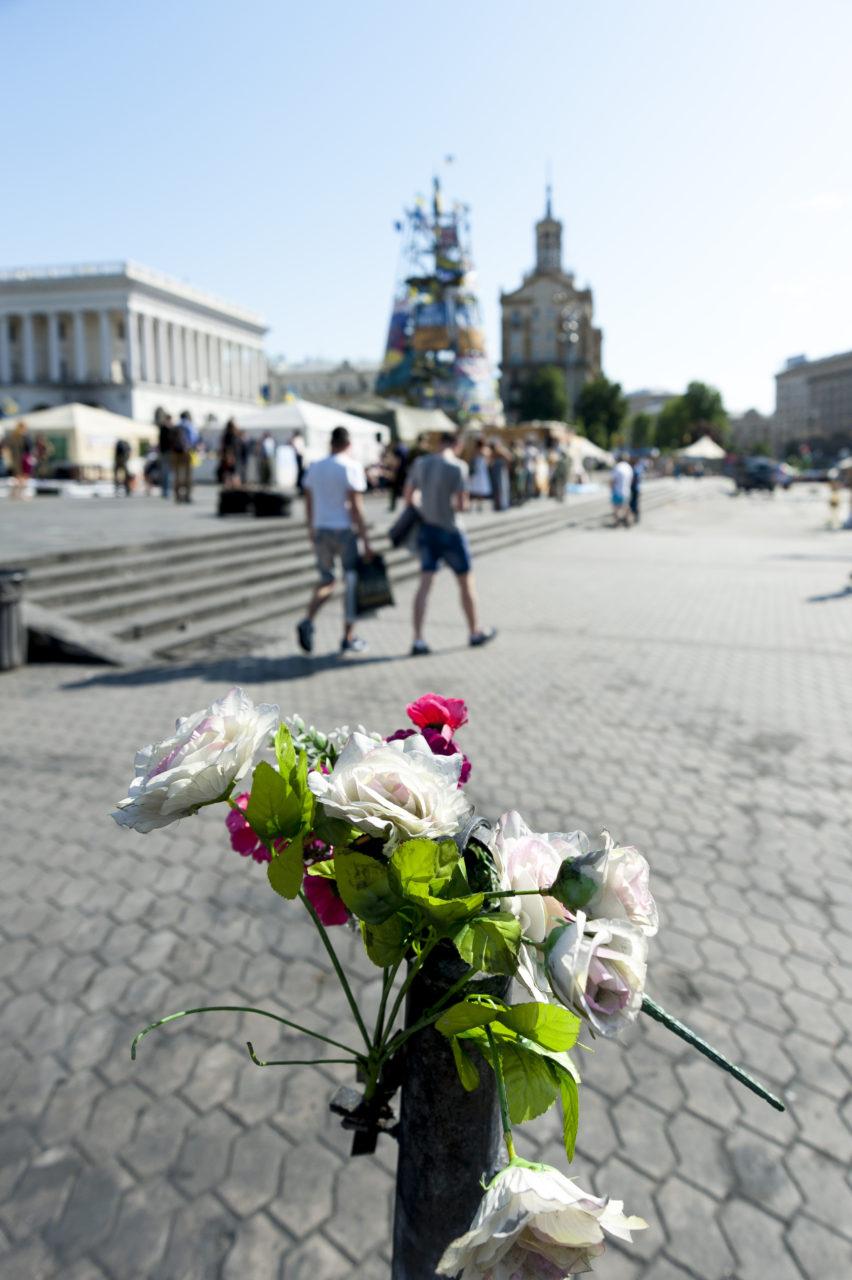Ukraina, Kiev/Kyiv. På bilden: Upp från det stora Frihets-torget, Majdan, i centrala Kiev löper Institutkagatan, alldeles intill det väldiga Hotel Ukraïna. Längs den gatan flöt vanliga människors blod den 20 februari 2014, då den paramilitära polisen Berkut placerade ut prickskyttar som döda omkring ett hundra personer från sina skyddade platser uppe i hotellbyggnaden (till höger utanför bilden). På bilden en av tusentals buketter till minne av de som dog den dagen – och alla andra som skadades och dog under striderna; torget bevakas och patrulleras av män som fortfarande bor på torget; många av dem klassas som krigsskadade med posttraumatiskt stressyndrom. Foto: Johan Lindstén
